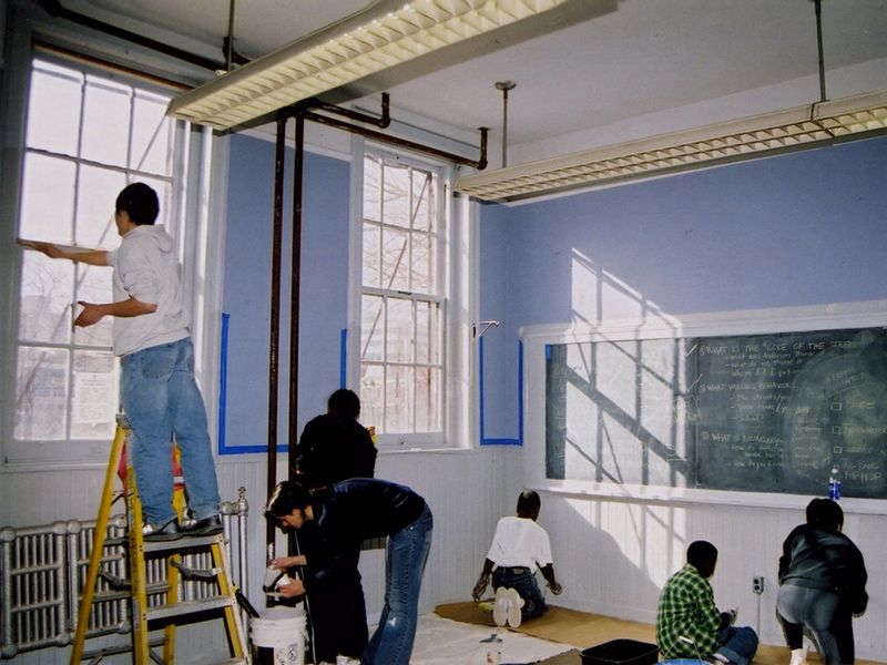 volunteers painting the walls of a classroom