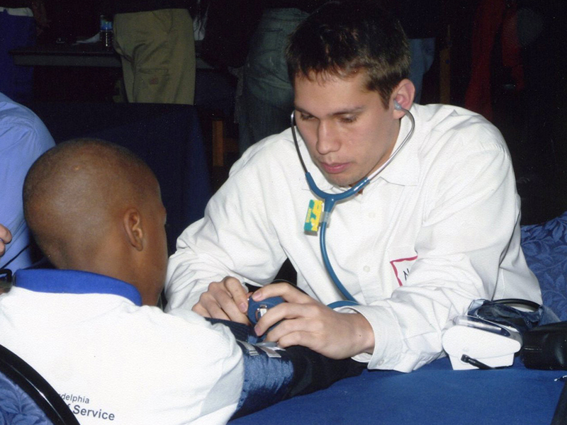 volunteer health professional giving a young man a health screening