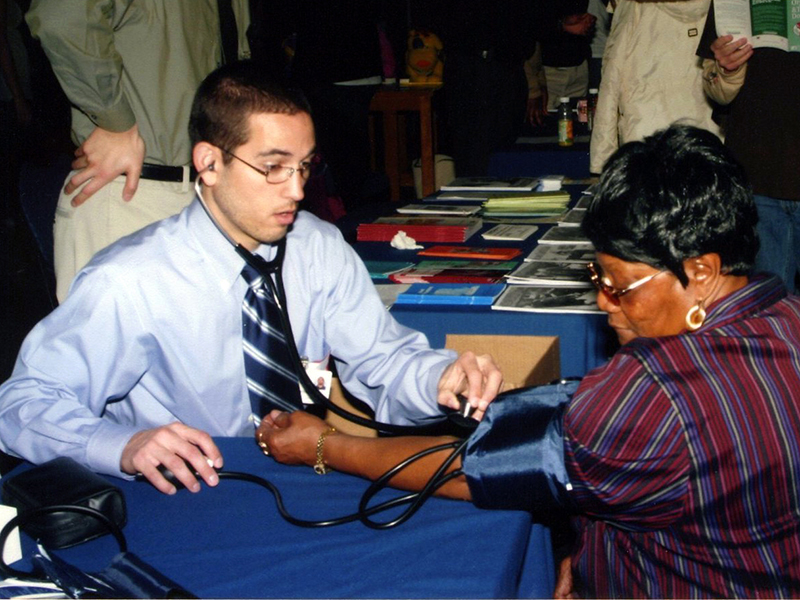 volunteer health professional giving a woman a health screening